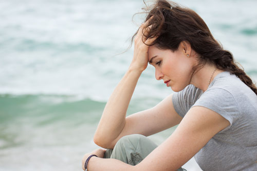 Depressed lady sitting on the beach with her head in her hand